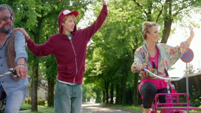 slo mo ts boy auf einem skateboard, das von seinem vater auf dem fahrrad gezogen wird und seine schrullige mutter, die ein fahrrad neben ihnen fährt - männlicher teenager stock-videos und b-roll-filmmaterial