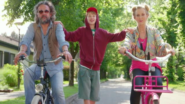 彼の風変わりな両親と一緒に通りを走るスケートボード上のslo mo ts少年 - 14歳から15歳点の映像素材/bロール