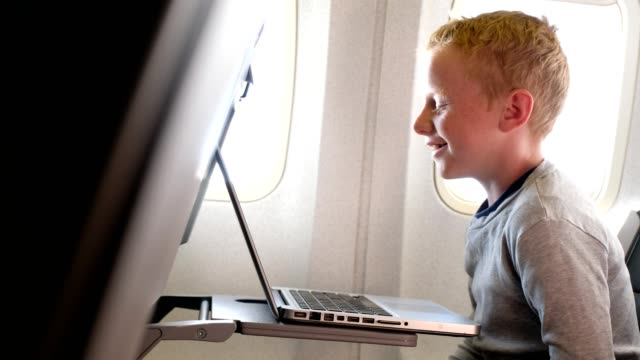 Jongen op het vliegtuig kijken naar een video op een computer