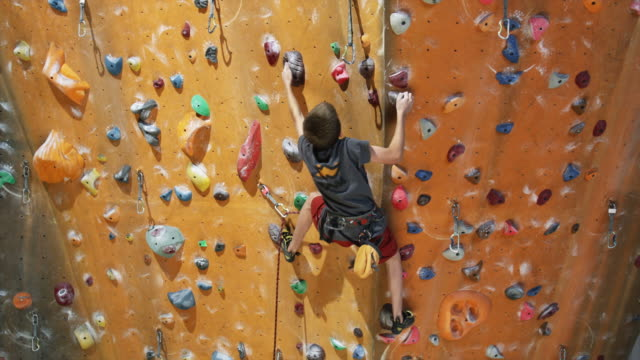 boy on an indoor climbing wall - kletterwand kletterausrüstung stock-videos und b-roll-filmmaterial