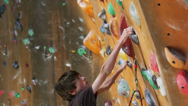 boy on an indoor climbing wall - felsklettern stock-videos und b-roll-filmmaterial