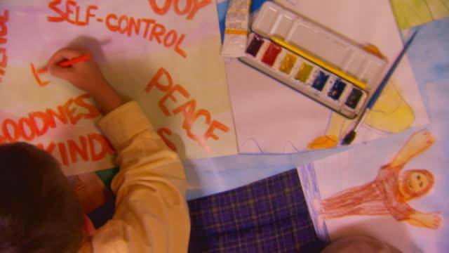 vídeos y material grabado en eventos de stock de boy on bed writing on poster - autodisciplina