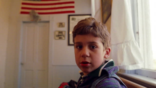 ms portrait boy on bench in schoolhouse turns to camera + smiles / american flag on wall in background - testa video stock e b–roll