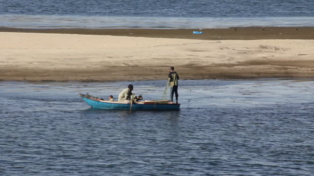 MS Boy on fishing boat with father and young child pulling in fishing net / Aswan, Egypt