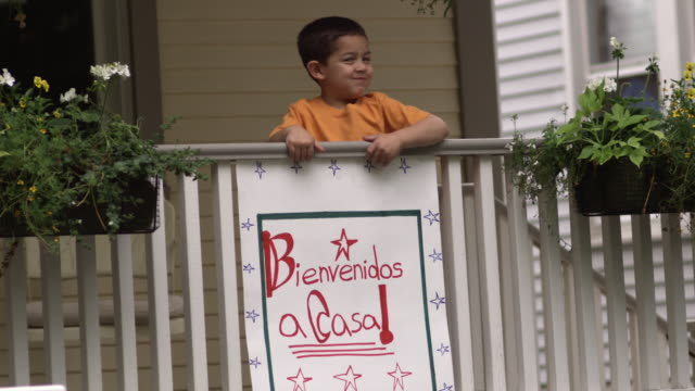 SM MS Boy on porch with 'Bienvenidos a Casa!' sign hanging over railing/ Boy waving as woman pulls him over to family/ Chicago, IL