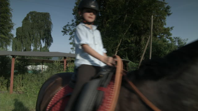 Boy on ranch learns how to ride a horse