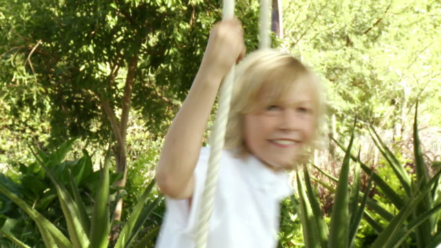 cu boy (8-9) on rope swing, cape town, south africa - solo un bambino maschio video stock e b–roll