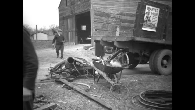 boy on second story of barn throws down piece of scrap metal to ground / three shots of abandoned farm equipment / man piling up pieces of scrap... - altmetall stock-videos und b-roll-filmmaterial