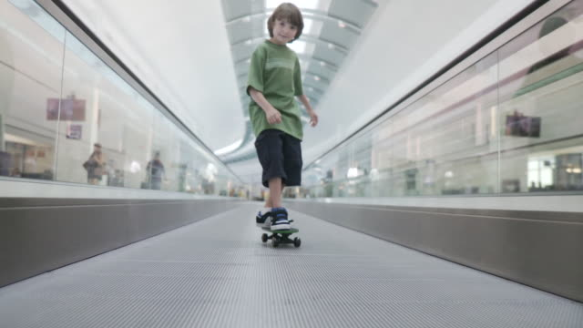 ms pov boy on skateboard to riding moving walkway in airport / jacksonville, fl, united states - rolltreppe stock-videos und b-roll-filmmaterial