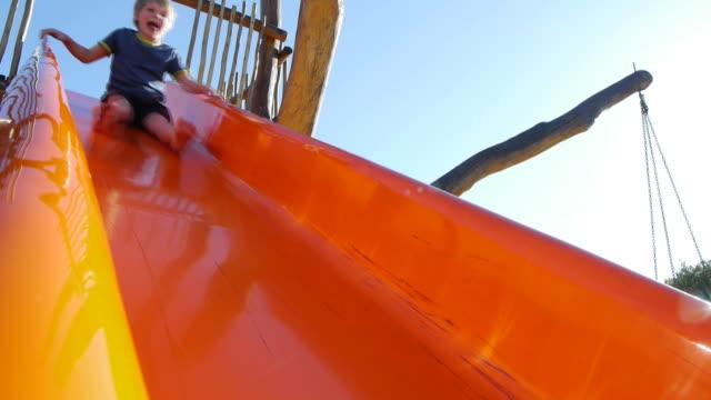 vidéos et rushes de garçon sur le toboggan - toboggan