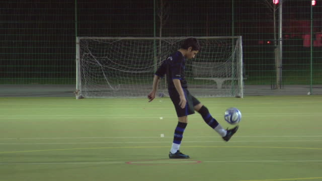 ws boy (14-15) on soccer field doing keep-ups, london, uk - ball stock-videos und b-roll-filmmaterial