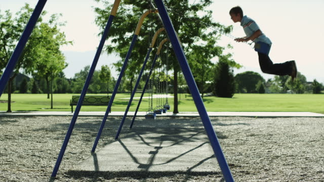 WS PAN Boy (12-13) on swing in park / Orem, Utah, USA