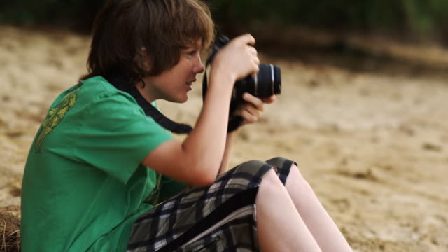 boy on the beach taking pictures - one teenage boy only stock videos & royalty-free footage