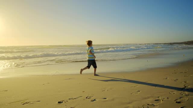 vídeos y material grabado en eventos de stock de niño en la playa  - toma ancha