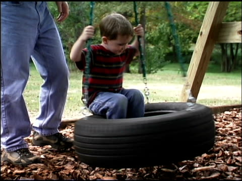 boy on tire swing at playground - tyre swing stock videos & royalty-free footage