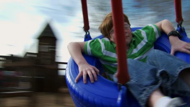 vidéos et rushes de boy on tire swing spinning - balançoire pneu
