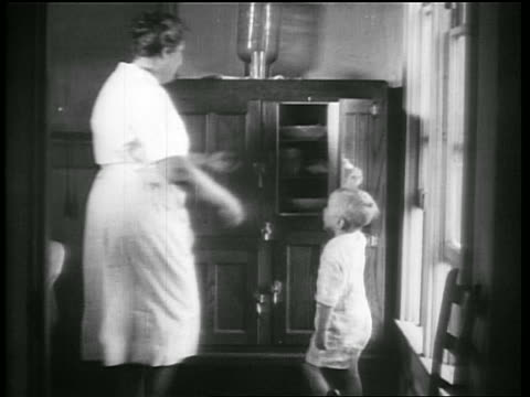 vidéos et rushes de b/w 1928 boy opening door to icebox / woman takes out dish + gives boy food / oklahoma / newsreel - grand mère