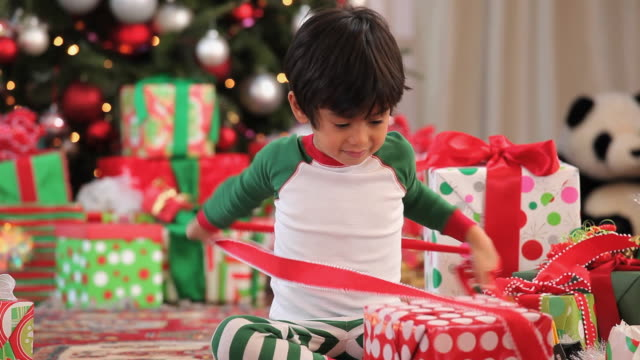 ms pan tu boy (2-3) opening presents on christmas morning / richmond, virginia, usa - child sitting cross legged stock videos & royalty-free footage