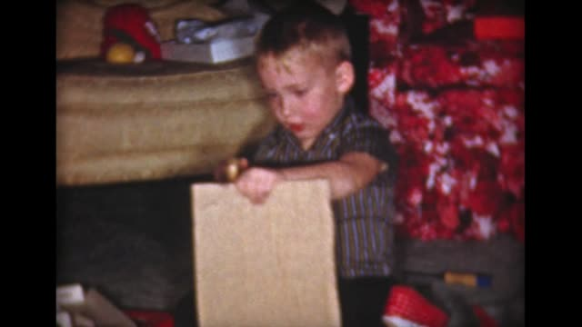 1959 boy opens Xmas present, uses toy saw
