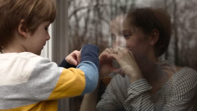 boy outside looking through glass window at mother in quarantine making heart sign - quarantena video stock e b–roll
