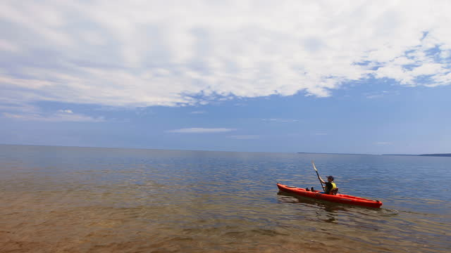 boy paddles across lake superior in kayak and runs hand through clear water on beautiful sunny day. - lago superiore video stock e b–roll