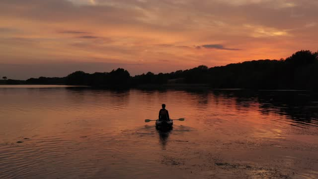 boy paddles in his kayak at sunset on pickmere lake, cheshire, on june 01 in knutsford, united kingdom. warm weather across the uk has seen thousands... - barca da diporto video stock e b–roll