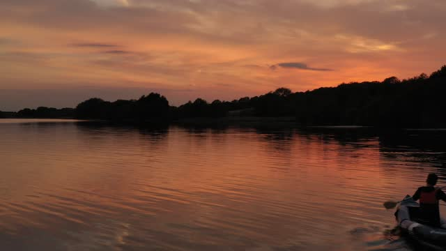 boy paddles in his kayak at sunset on pickmere lake, cheshire, on june 01 in knutsford, united kingdom. warm weather across the uk has seen thousands... - twilight stock videos & royalty-free footage