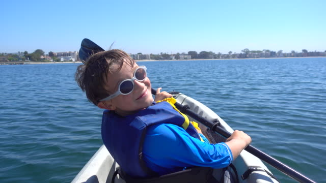 a boy paddling in a kayak in mission bay, san diego. - life jacket stock videos & royalty-free footage