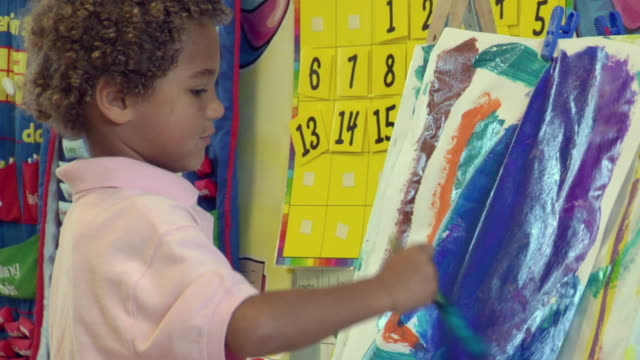 ms td boy painting on easel in preschool classroom / san antonio, texas, usa - school bulletin board stock videos and b-roll footage