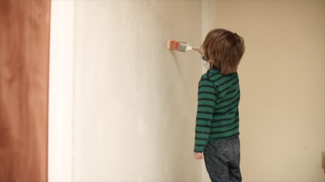 vídeos de stock e filmes b-roll de boy painting white wall holding paint brush - bricolage