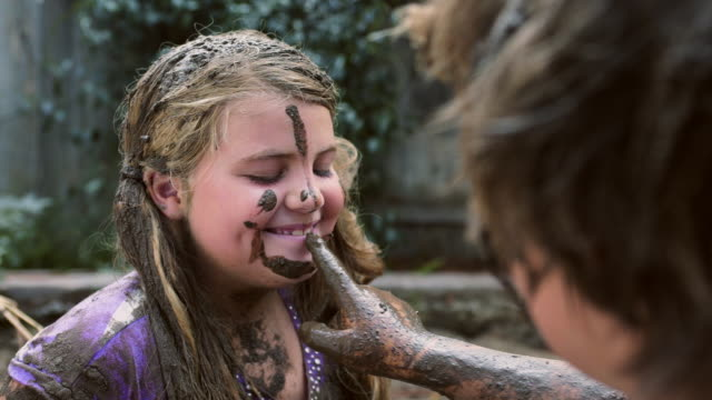 boy paints mud on sisters face - cu coverage on girl - messy stock videos and b-roll footage