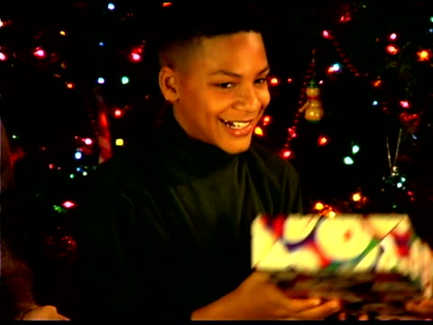 stockvideo's en b-roll-footage met boy passing out christmas gifts - doorgeven