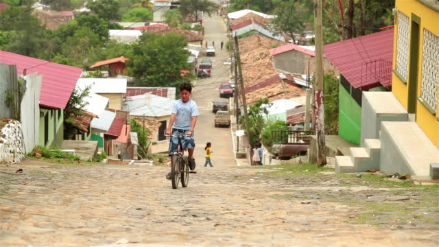 Boy pedals bike up cobblestone street in third-world country (slow-motion)