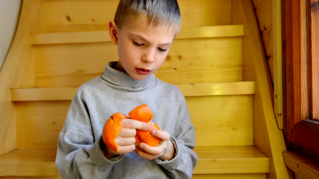 stockvideo's en b-roll-footage met boy peeling a tangerine - schil