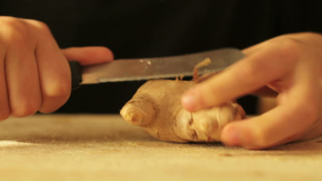 Boy peeling ginger