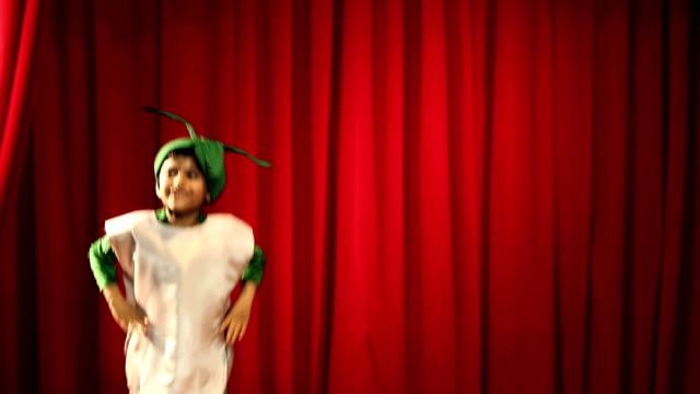 ms boy performing on stage wearing radish costume during annual day - カーテン レース点の映像素材/bロール