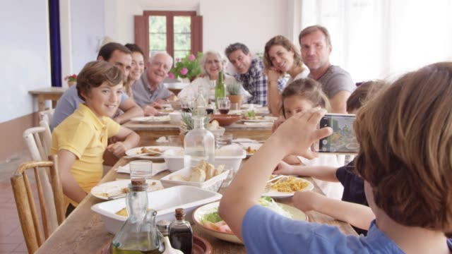 vídeos de stock e filmes b-roll de boy photographing family on phone at dining table - homens adultos