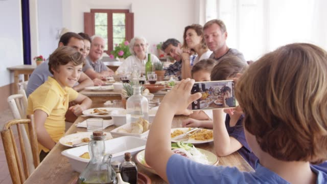 boy photographing family through phone at table - grandchild stock videos & royalty-free footage