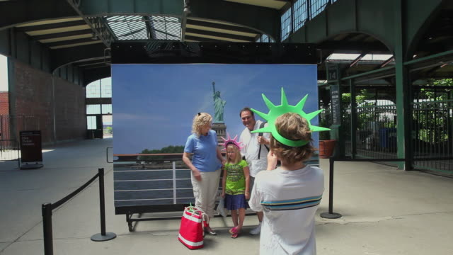 ms boy (10-11) photographing parents with daughter (6-7) in front of picture of statue of liberty / new york city, new york, usa - statue of liberty new york city stock videos & royalty-free footage