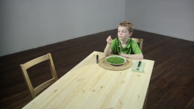 Boy picking pea off his plate and flicking it off table