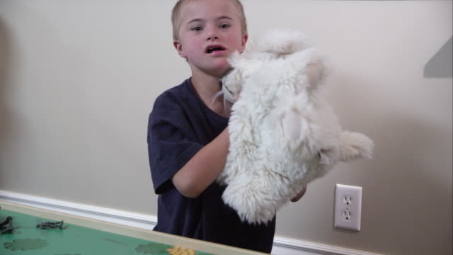 vídeos de stock e filmes b-roll de boy picking up and throwing a white stuffed animal. - presidente de empresa