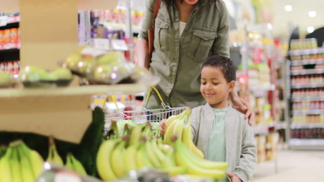Boy picking up bananas in grocery store