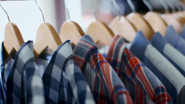 boy picks out plaid button-down from shirt rack in trendy clothing shop - タータンチェック点の映像素材/bロール