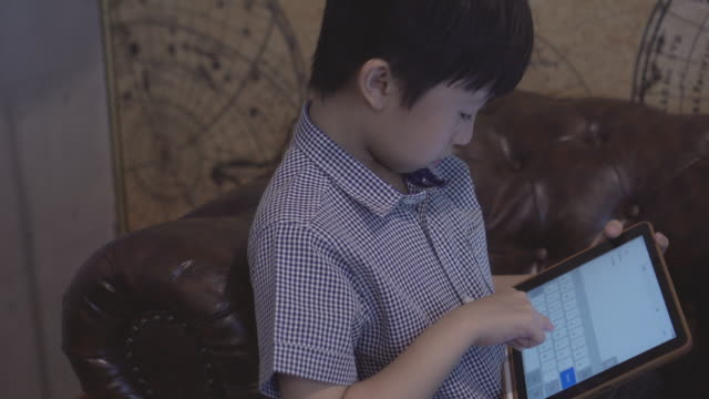 stockvideo's en b-roll-footage met jongen spelen digitale tablet alleen met kopieer ruimte - generation z