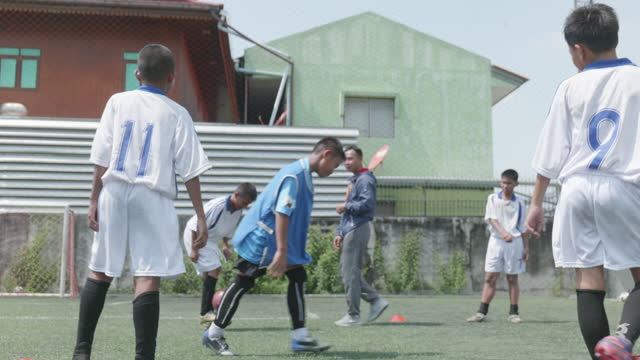 boy play soccer game, footballers are warming up their bodies before playing. - education building stock videos & royalty-free footage