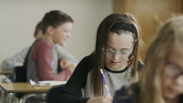 Boy playfully pulling hair of girl studying in classroom / Provo, Utah, United States