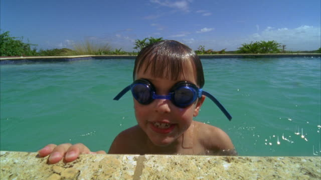 CU, Boy (6-7) playing and swimming in pool, Vieques, Puerto Rico