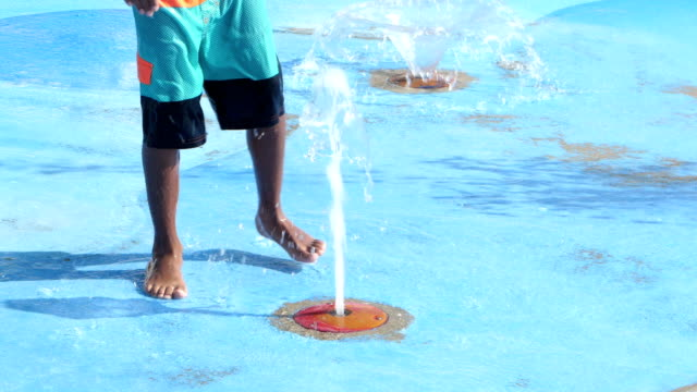 boy playing at water park in fountain - fountain stock videos and b-roll footage