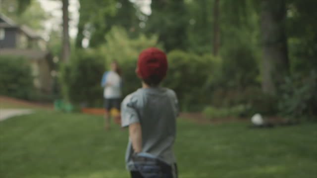 boy playing catch with his father - fangen stock-videos und b-roll-filmmaterial