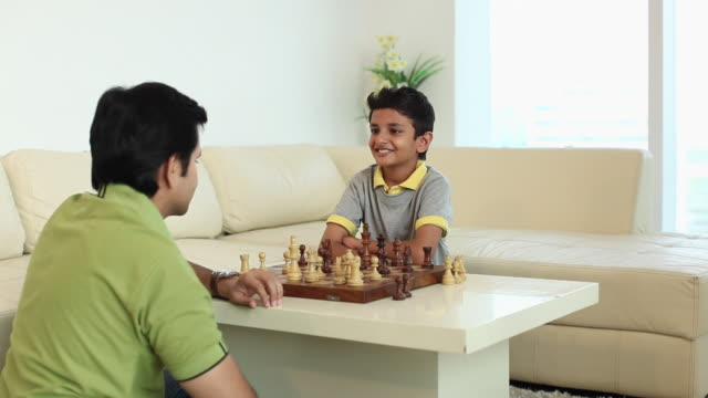 boy playing chess with his father  - game night leisure activity stock videos & royalty-free footage